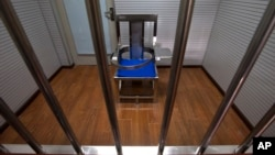 FILE - A chair specially designed to restrain inmates is seen behind bars in an interrogation room at the Number One Detention Center in Beijing, Oct. 25, 2012.