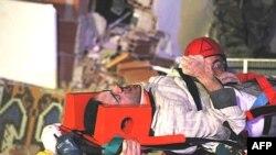 Рятувальники несуть учителя, якого знайдено під обваленим будинком