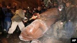Para demonstran oposisi Ukraina merusak monumen Vladimir Lenin di Kiev, Ukraina hari Minggu (8/12).