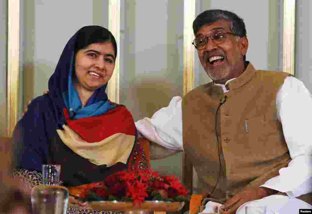 Nobel Peace Prize laureates Kailash Satyarthi (R) and Malala Yousafzai react during a news conference in Oslo Dec. 9, 2014.