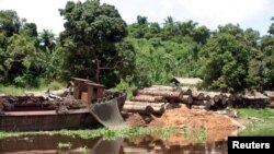 FILE - Logs lie next to a rusting barge on the banks of the Congo River, Oct. 7, 2004. Greenpeace reported at the time that the president of the Democratic Republic of the Congo was finally backing a largely ignored ban on new logging that had been approved in 2002. But several illegal permits have been issued since then.