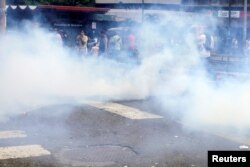 People run away from tear gas during riots for food in Caracas, Venezuela, June 2, 2016.