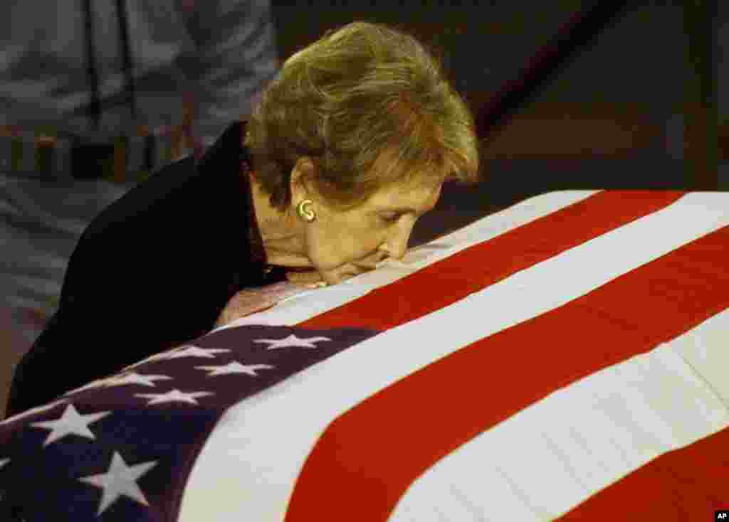 Former first lady Nancy Reagan kisses the casket of her husband former President Ronald Reagan prior to the removal of his remains from the Capitol Rotunda in Washington, June 11, 2004.