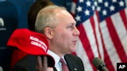 """FILE - House Majority Whip Steve Scalise of Louisiana displays a """"Make America Great Again"""" hat while speaking with reporters on Capitol Hill in Washington after a House Republican leadership meeting, Nov. 15, 2016. Donald Trump 2016 presidential campaign owns the phrase."""