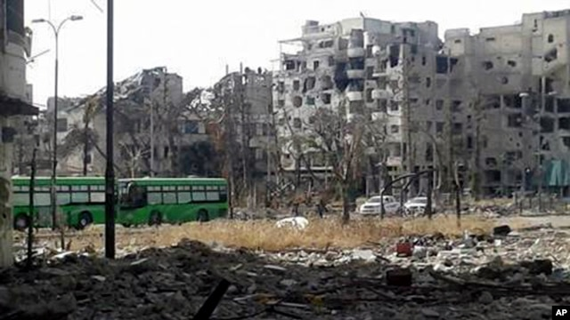 This May 7, 2014 photo provided by the Coordination Committee of Khalidiya Neighborhood in Homs shows green buses carrying Free Syrian Army fighters  leaving Homs, Syria.