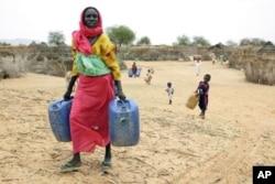 Darfur woman carries water.