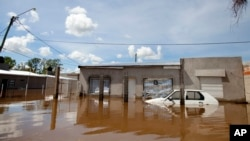 A car and homes are submerged in floodwater in Concordia, Argentina, Dec. 28, 2015.