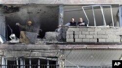 Binh sĩ Israel tại các căn hộ trong khu chung cư bị phá hủy bởi rocket từ dải Gaza.