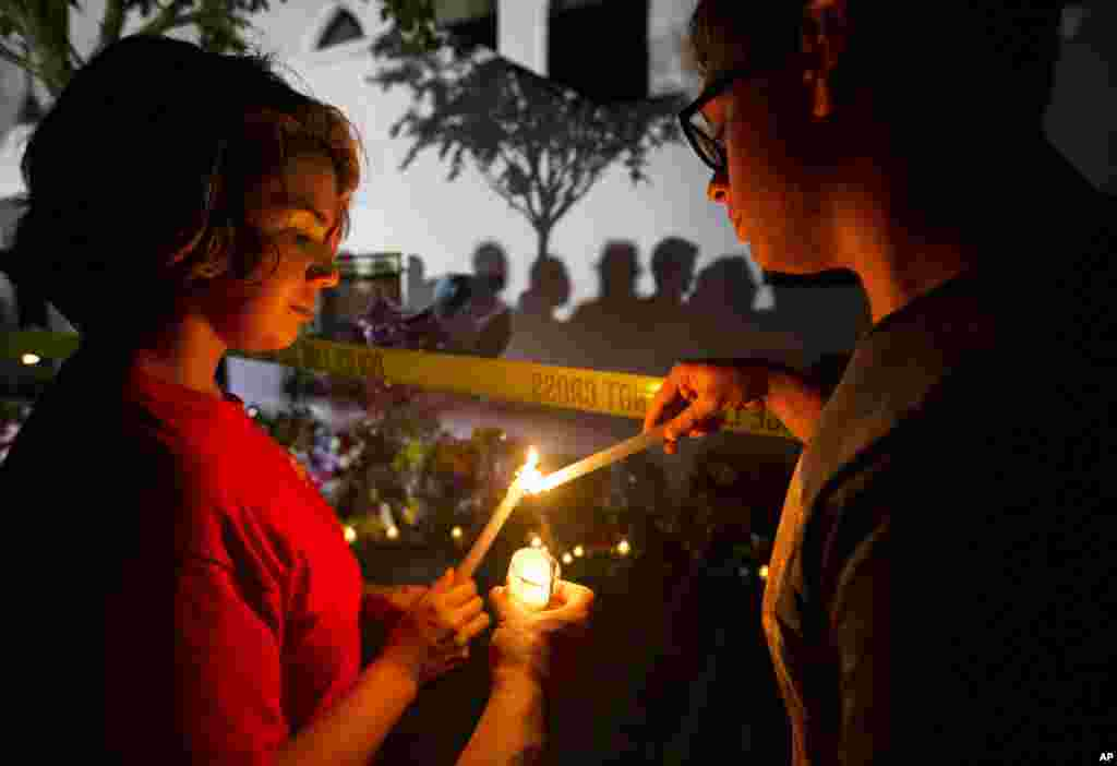 Olina Ortega, left, and Austin Gibbs light candles at a sidewalk memorial in front of Emanuel AME Church where people were killed by a white gunman Wednesday during a prayer meeting inside the historic black church in Charleston, S.C., June 18, 2015.