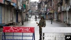Tentara Paramiliter India berjaga di jalan sepi saat jam malam di Srinagar, Kashmir yang dikuasai India, Kamis, 8 Agustus 2019.