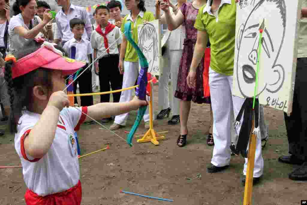 '국제아동절'인 1일 북한 평양의 '9.15 보육원'에서 운동회가 열린 가운데, 한 어린이가 바락 오바마 미국 대통령을 그린 표적을 향해 활을 쏘는 게임을 하고 있다. 옆에는 박근혜 한국 대통령을 그린 표적이 걸려있다.