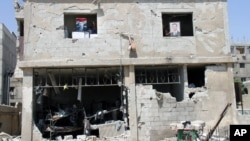 Syrian security forces officers hold portraits of Syrian President Bashar Assad from the windows of their building, which was destroyed after a car bomb exploded near the shrine of Sayyida Zeinab, in a suburb of Damascus, Syria, June 14, 2012.