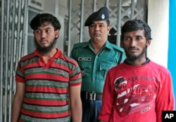 A Bangladeshi policeman escorts Jikrullah, left, and Ariful Islam, suspects in the hacking death of blogger Washiqur Rahman Babu, in Dhaka, March 30, 2015.
