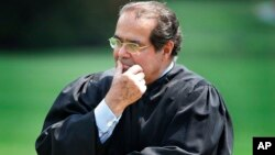 FILE - In this 2006 photo, Supreme Court Justice Antonin Scalia listens to President Bush speak during a ceremony at the White House.