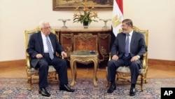 El presidente de la Autoridad Palestina, Mahmoud Abbas, izquierda, conversa con el presidente egipcio Mohammed Morsi, en El Cairo. Luego del cese al fuego con Israel, Hamas ha ofrecido su apoyo a Abbas.