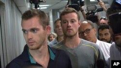 Dua perenang Olimpiade AS, Gunnar Bentz(kiri) dan Jack Conger meninggalkan kantor polisi di bandara Rio de Janeiro, Rabu (17/8).