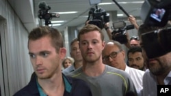 Dua perenang Olimpiade AS, Gunnar Bentz (kiri) dan Jack Conger meninggalkan kantor polisi di bandara Rio de Janeiro, Rabu (18/8). (AP/Mauro Pimentel)