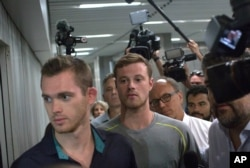 Journalists surround American Olympic swimmers Gunnar Bentz, left, and Jack Conger, center, as they leave the police station at Rio International airport early Aug. 18, 2016.