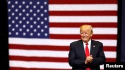 도널드 트럼프 대통령이 지난 6월 아이오와주 시더래피즈에서 지지자들이 모인 행사 연단에 올라 두손을 맞잡고 있다.