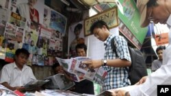 Customers buy local weekly journals at a roadside shop in Rangoon, Burma, Aug. 20, 2012.