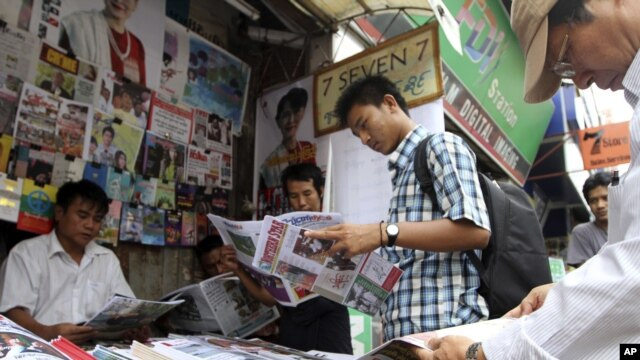 Customers buy local weekly journals at a roadside shop in Rangoon, Burma, Aug. 20, 2012.
