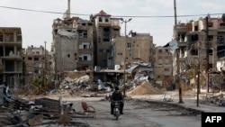 一名男子2月10日骑摩托车经过残破不堪的哈拉斯塔市(Harasta)。这座城市位于叙利亚首都大马士革以东。