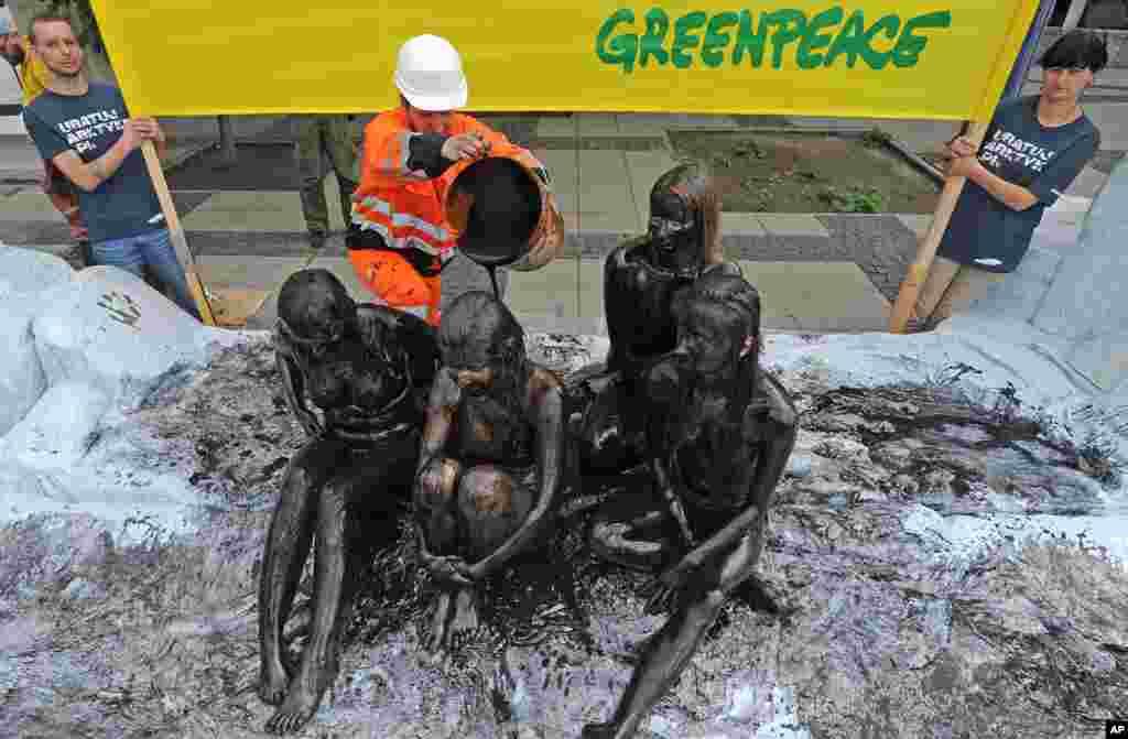 Aktivisti Greenpeace-a activist, obučeni kao radnici naftnih kompanija, posipaju naftom druge aktiviste protestirajući na taj način protiv naftnih bušenja u Arktičkom moru.