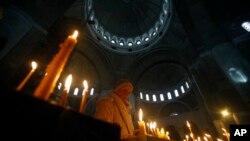 Žena pali sveću u Hramu svetog Save, 6. januar 2015.