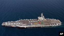 El portaaviones USS George H.W. Bush navega acompañado por un crucero y un destructor, ambos dotados con lanzamisiles.