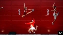 FILE - A young girl mimics the pose of a Chinese Olympic athletes depicted in Coca-Cola advertising, at the Olympic green in Beijing, Aug. 20, 2008.