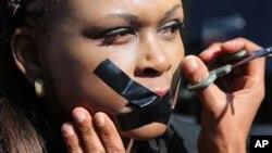 Demonstran menyelotip mulutnya di Johannesburg dalam protes di luar kantor South African Broadcasting Corporation (SABC) (1/7). (AP/Denis Farrell)