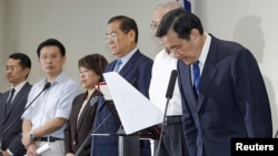 Taiwan President Ma Ying-jeou, right, bows during a news conference with party officials after the ruling Kuomintang (KMT) party was defeated in the local elections in Taipei, Nov. 29, 2014.