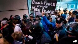Los manifestantes, rodeados de policías y viajeros, pasaron por una salida de la Terminal 4 del Aeropuerto Internacional John F. Kennedy en Nueva York, el sábado 28 de enero, luego de que dos refugiados iraquíes fueran detenidos mientras trataban de entrar el país.