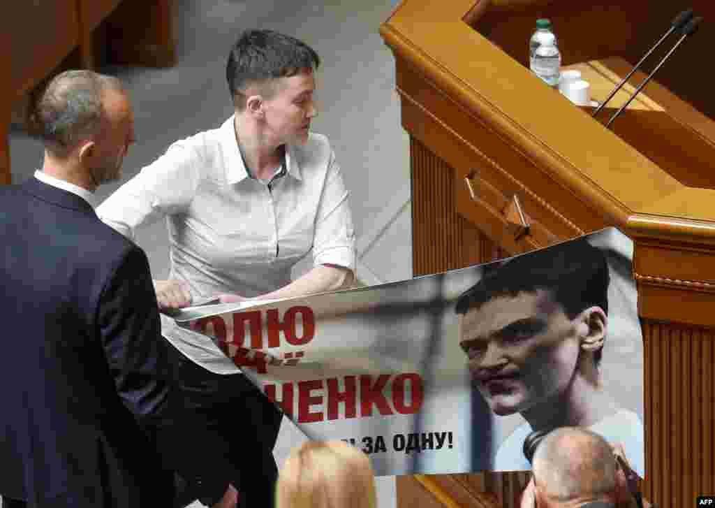 នាង Nadiya Savchenko អ្នកបើកយន្តហោះរបស់អ៊ុយក្រែនដោះបដាដែលមានរូបនាងចេញ ពីវេទិកានៅសភាអ៊ុយក្រែន នៅក្នុងក្រុង Kyiv។
