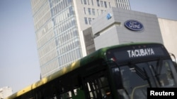 A bus passes in front of a Ford logo near a sales store of the automaker in Mexico City, Mexico, April 5, 2016.