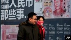 Un couple passe devant un écran montrant les caractéristiques de sécurité de la nouvelle coupure de 100 Yuan. Beijing, le lundi 11 janvier 2016 .