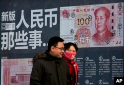 FILE - A couple walk past a display showing the security features of the new 100 Yuan note in Beijing, Monday, Jan. 11, 2016.