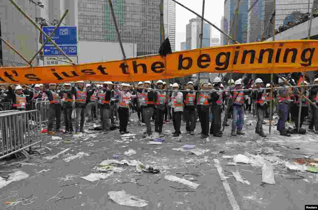 Um cartaz gigante é removido da área que tinha sido bloqueada pelos manifestantes pró-democracia. Dez 11, 2014.