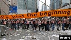 Công nhân dỡ bỏ một biểu ngữ với hàng chữ 'Chỉ mới bắt đầu' tại một địa điểm biểu tình ủng hộ dân chủ của người dân Hong Kong, 11/12/14
