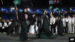 Saudi Arabia's Wojdan Ali Seraj Abdulrahim Shaherkani, center, opening ceremony of the 2012 Summer Olympics, London, July 27, 2012.