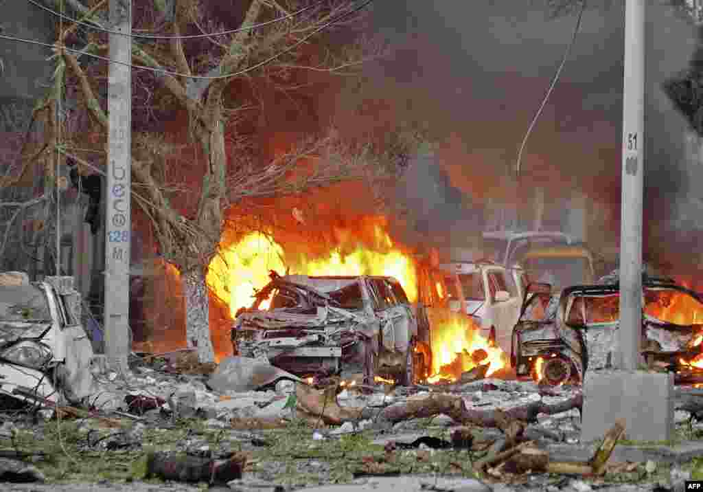 Wrecked cars burn at the scene of a terror attack at the Ambassador Hotel in Mogadishu, Somalia, after a car bomb exploded, killing several people.