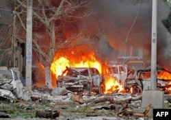 FILE - Wrecked cars burn at the scene of a terror attack at the Ambassador Hotel, after a car bomb exploded on June 1, 2016 at a top Mogadishu hotel that houses several MPs, killing several people, and followed by a gun battle.