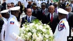 12일 아이티 포르토 프랭스를 방문한 프랑스아 올랑드 프랑스 대통령(가운데 왼쪽)이 미첼 마르텔리 아이티 대통령과 함께 화환을 놓고 있다.
