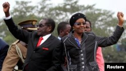 FILE: Zimbabwean President Robert Mugabe and his wife Grace wave to supporters and guests during celebrations to mark his 90th birthday, Marondera,Feb. 23,2014.