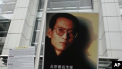 Activists hold a picture of Liu Xiaobo outside the China's liaison office in Hong Kong.