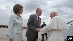 In this picture made available by the Vatican newspaper Osservatore Romano, Spain's King Juan Carlos, next to Queen Sofia welcomes Pope Benedict XVI upon his arrival at Madrid's Barajas airport, August 18, 2011