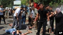 Petugas memeriksa warga Palestina yang tewas dan cedera di luar sekolah PBB di Rafah, Jalur Gaza selatan, Minggu, 3 Agustus 2014.