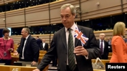 "Nigel Farage, the leader of the United Kingdom Independence Party, holds the British flag as he attends a plenary session at the European Parliament on the outcome of the ""Brexit"" in Brussels, Belgium, June 28, 2016."