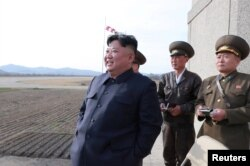FILE - North Korean leader Kim Jong Un, along with two military officials, observes a Korean People's Air Force training flight, on April 16, 2019. Photo released April 17, 2019 by North Korea's Central News Agency (KCNA).