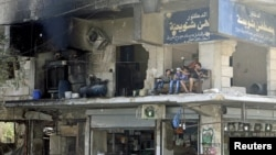 FILE - Residents sit on the balcony of a damaged building in Aleppo's al-Shaar neighborhood, Syria, Aug.1, 2015.